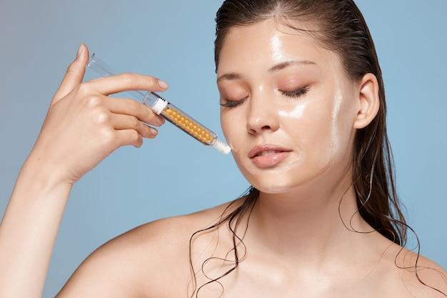 Frau mit nassen haaren und gesicht hält spritze mit geschlossenen augen