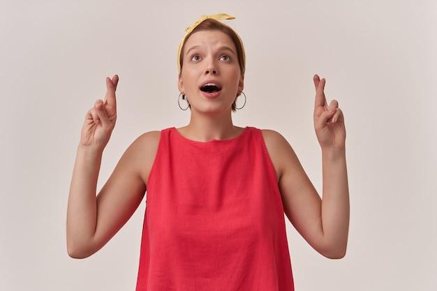 Frau mit natürlichem make-up, das stilvolles trendiges rotes hemd und braune augen der gelben bandana-dame trägt, die oben mit dem finger gekreuzten posen-gefühlsgebet nachschlagen