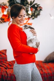 Frau mit niedlichem häschen durch weihnachtsbaum