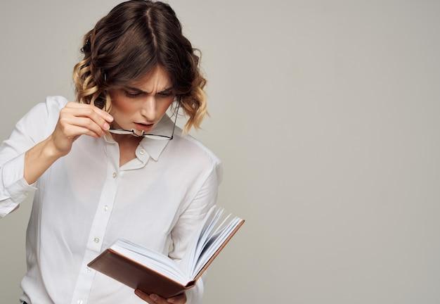 Frau mit notizblock in händen geschäftsfinanzierungsbrille auf ihrem gesicht