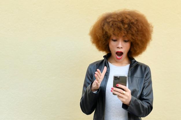 Frau mit offenem mund, die auf ihr telefon schaut