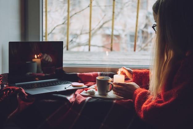 Frau mit online-dating-app auf laptop. valentinstag, dating, treffen während des coronavirus-ausbruchs. liebe auf distanz in zeiten des coronavirus.