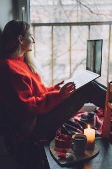 Frau mit online-dating-app auf laptop. valentinstag während des coronavirus-ausbruchs. liebe auf distanz, einsamkeit in selbstisolation in zeiten des coronavirus.