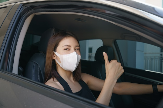 Frau mit op-maske im auto, zum schutz vor coronaviren oder covid-19.