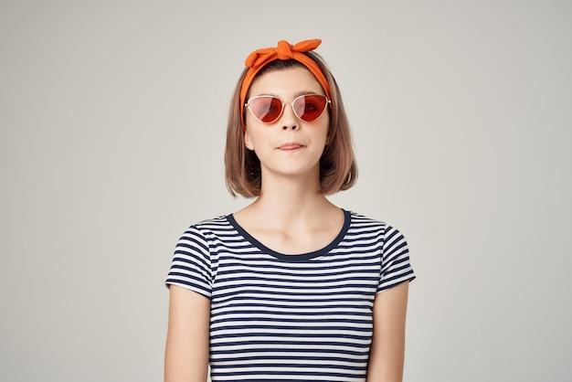 Frau mit orangefarbenem stirnband mit sonnenbrille im modernen stil