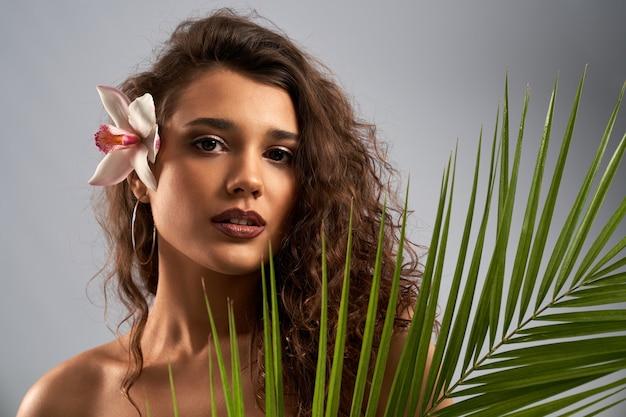 Frau mit orchidee hinter ohr, die palmblatt hält