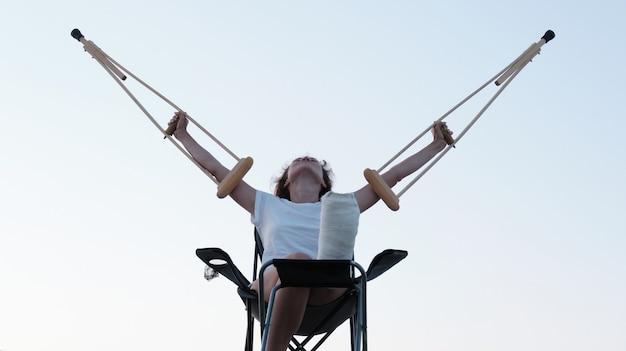 Frau mit orthopädischen krücken über dem kopf beinverletzung rehabilitation nach einer fraktur