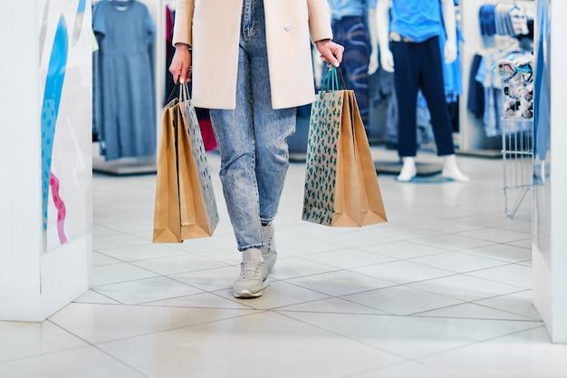 Frau mit papiereinkaufstaschen, die im modernen einkaufszentrum gehen. mädchen, das einkaufstaschen beim gehen am laden trägt.