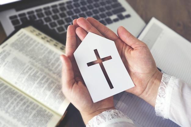 Frau mit papierkirchensymbol, die im glauben mit computer-laptop betet, online-konzept für kirchendienste, online-kirche zu hause, spiritualität und religion.