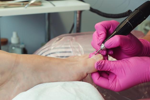 Frau mit pediküre im salon frau entspannt sich im salon und kümmert sich um nägel professionelle pediküre