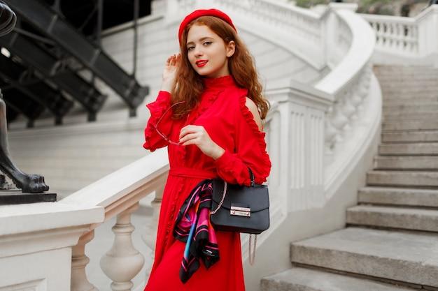 Frau mit perfektem lächeln, roten haaren und großen augen. rote baskenmütze tragen.
