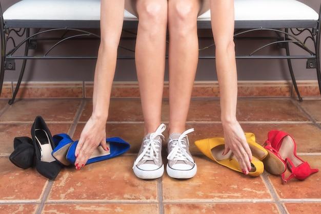 Frau mit perfekten, schlanken beinen, die bequeme sneakers statt unbequemer schuhe mit hohen absätzen wählt.