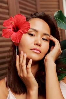 Frau mit perfekter haut und hibiskusblüte in den haaren, die über holzwand und tropischen pflanzen aufwerfen.