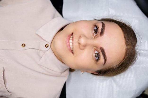 Frau mit permanent-make-up-tattoo auf ihren augenbrauen. close-up kosmetikerin lässt make-up eine grundierung auftragen. professionelles make-up und kosmetische hautpflege.