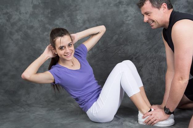 Frau mit persönlichem trainer, den das handeln sitzt, ups in turnhalle