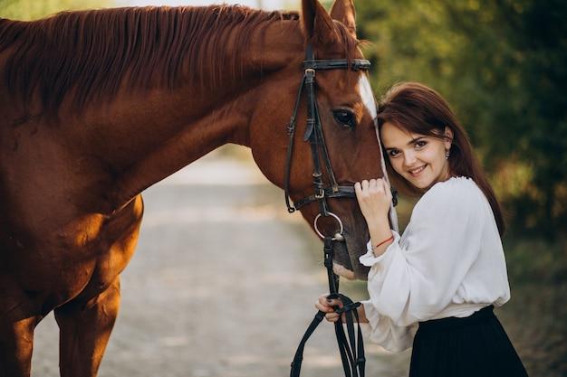Frau mit pferd im wald