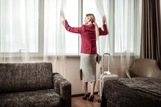 Frau mit pferdeschwanz. blonde frau mit langem pferdeschwanz, der rote jacke trägt, die nahe fenster im hotel steht