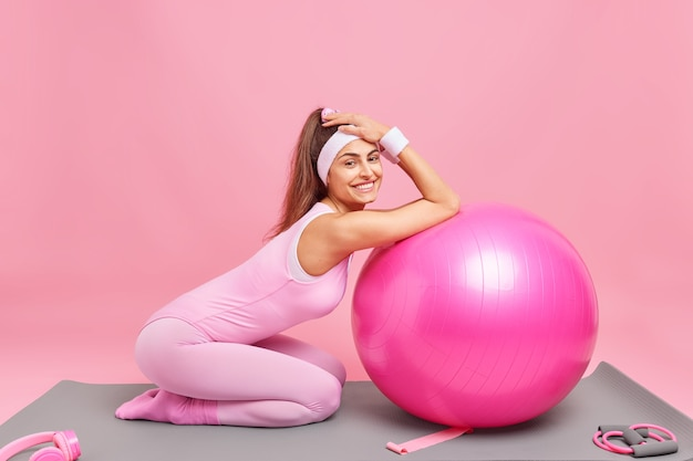 Frau mit pferdeschwanz stützt sich auf fitnessball und macht pause, nachdem das training einen aktiven lebensstil im anzug führt
