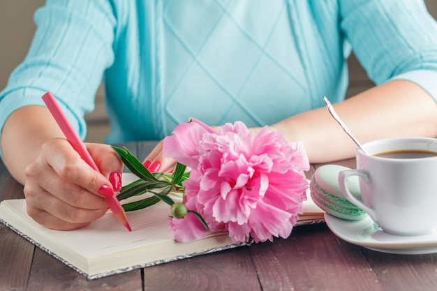 Frau mit pfingstrosenblume auf küche mit kaffee