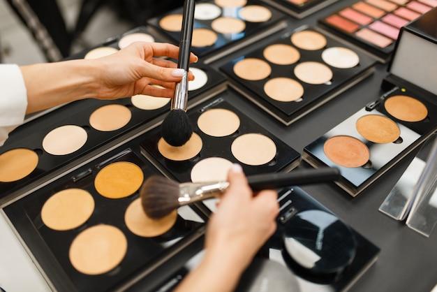 Frau mit pinsel, die puderton im kosmetikgeschäft wählt. käufer am schaufenster im luxus-schönheitssalon, kundin im modemarkt