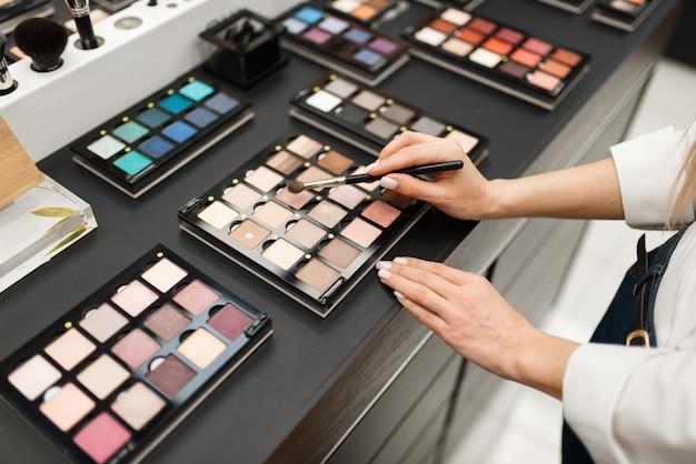 Frau mit pinsel, die schatten im kosmetikgeschäft wählt. käufer im luxus-schönheitssalon, kundin im modemarkt