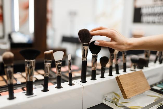 Frau mit pinsel, die schattenton im kosmetikgeschäft wählt. käufer im luxus-schönheitssalon, kundin im modemarkt