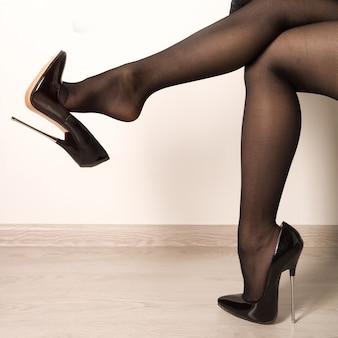 Frau mit prügel in schwarzen fetisch glänzenden lackleder stiletto high heels mit knöchelriemen - bild