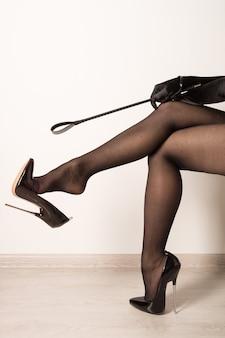 Frau mit prügel in schwarzen fetisch glänzenden lackleder stiletto high heels mit knöchelriemen