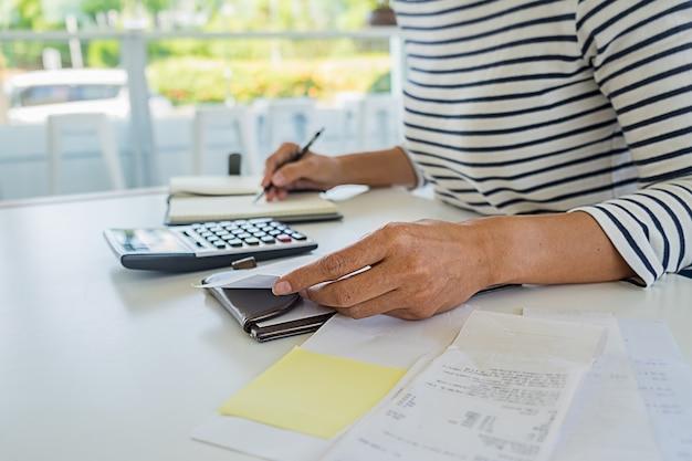 Frau mit rechnungen und taschenrechner. frau, die taschenrechner verwendet, um rechnungen am tisch im büro zu berechnen. kostenberechnung