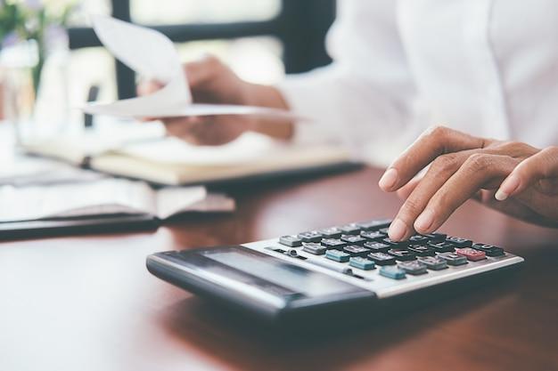 Frau mit rechnungen und taschenrechner. frau, die taschenrechner verwendet, um rechnungen am tisch im büro zu berechnen.