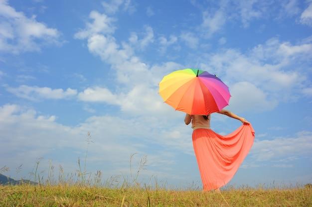 Frau mit regenbogenregenschirm und blauem himmel