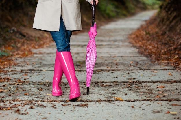 Frau mit regenschirm, der gummistiefel trägt