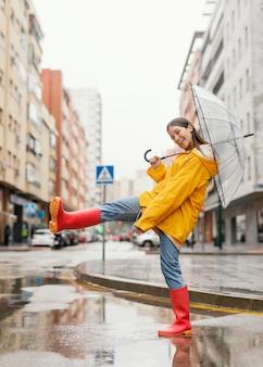 Frau mit regenschirm, der in der regenvorderansicht steht