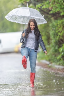 Frau mit regenschirm, die in regenstiefeln in einer pfütze bei starkem regen spaziert.