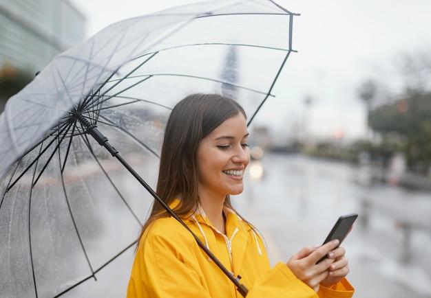 Frau mit regenschirm mit dem handy