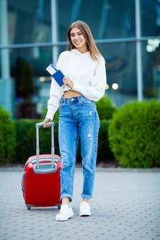 Frau mit reisepass und tickets in der nähe des flughafens