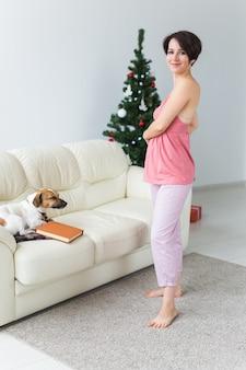 Frau mit reizendem hund im wohnzimmer mit weihnachtsbaum