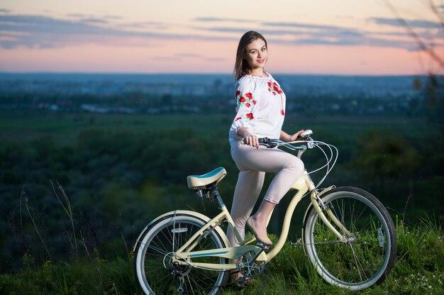 Frau mit retro- fahrrad auf dem hügel am abend
