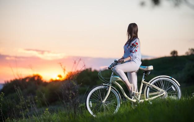 Frau mit retro fahrrad auf dem hügel am abend