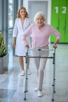 Frau mit rolling walker mit rehabilitationsverfahren in der klinik