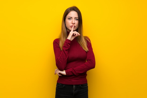 Frau mit rollkragen über der gelben wand, die ein zeichen der ruhegeste zeigt, die finger in mund setzt