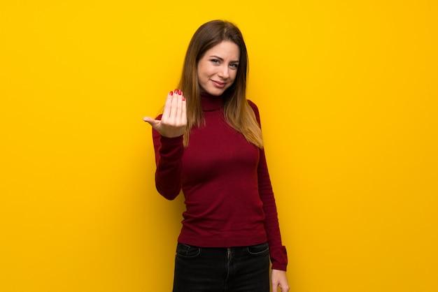 Frau mit rollkragen über gelber wand einladen, mit der hand zu kommen. glücklich, dass du gekommen bist