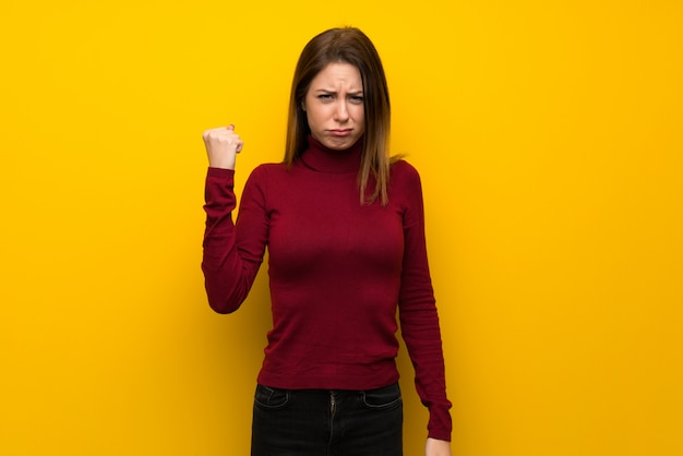 Frau mit rollkragen über gelber wand mit verärgerter geste
