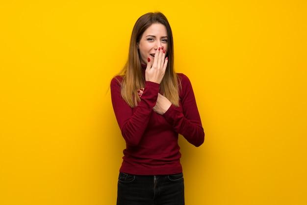 Frau mit rollkragenpullover über gelber wand leidet unter husten und fühlt sich schlecht