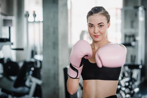 Frau mit rosa boxhandschuhen in der turnhalle