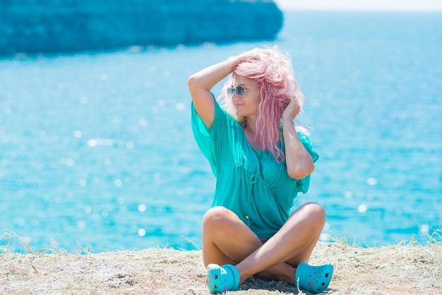 Frau mit rosa haaren, die auf dem berg sitzen