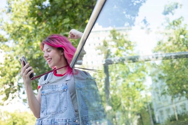 Frau mit rosa haaren, die draußen auf ihren handybildschirm schaut