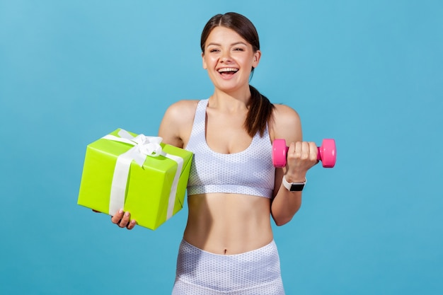 Frau mit rosa hantel und großer grüner geschenkbox, die an feiertagen eine mitgliedschaft im fitnessstudio erhält