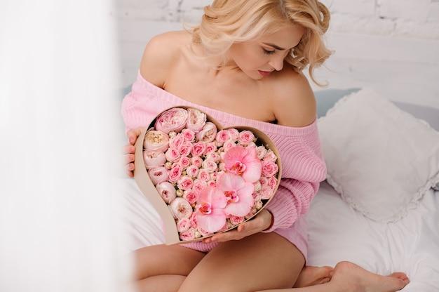 Frau mit rosa hemd sitzt auf dem bett und hält die herzförmige schachtel mit rosafarbenen pfingstrosen, orchideen und rosen