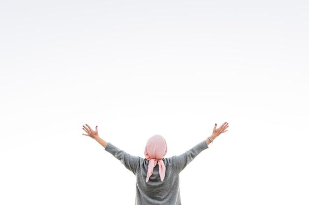 Frau mit rosa kopftuch, das den horizont betrachtet. krebskonzept